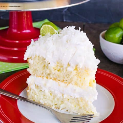 A slice of Key Lime Cake frosted with coconut buttercream in the center and on top