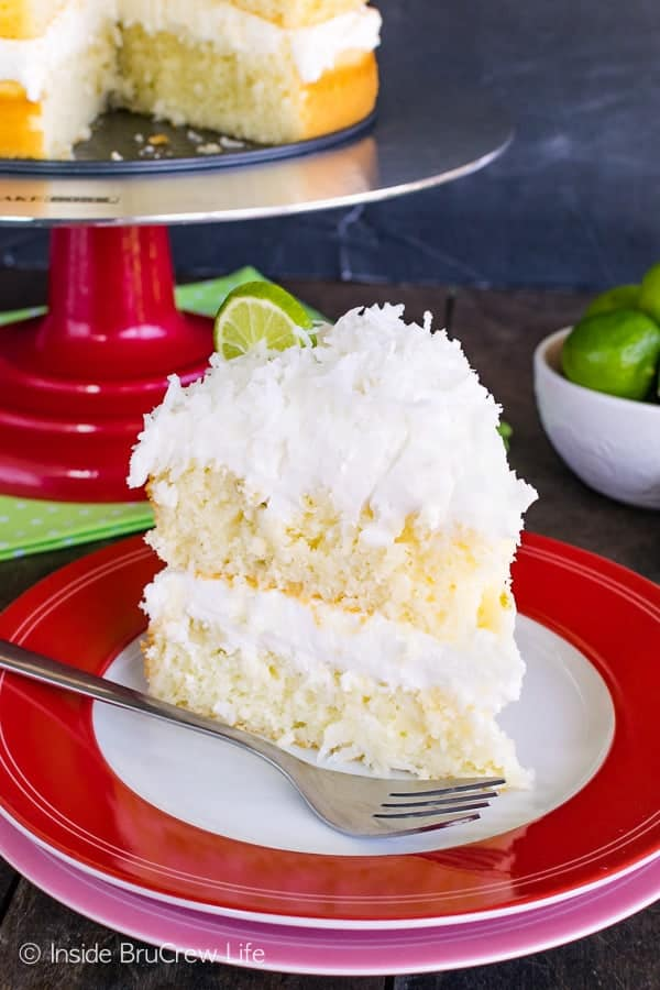 Coconut Key Lime Rum Cake - key lime cake layers topped with fluffy coconut frosting and a sweet rum glaze is a delicious recipe to share at spring and summer parties! #keylime #rumcake #coconut #layercake #cake #doctoredcakemix