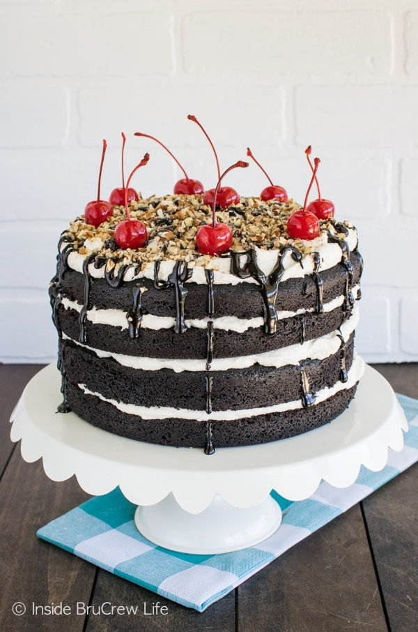 Cherries, pecans, and hot fudge add a fun topping to this Dark Chocolate Layer Cake. This is an absolutely perfect dessert recipe.