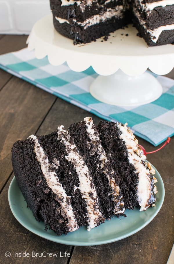 Layers of cake and frosting topped with hot fudge, pecans, and cherries make this Dark Chocolate Layer Cake the perfect dessert recipe!