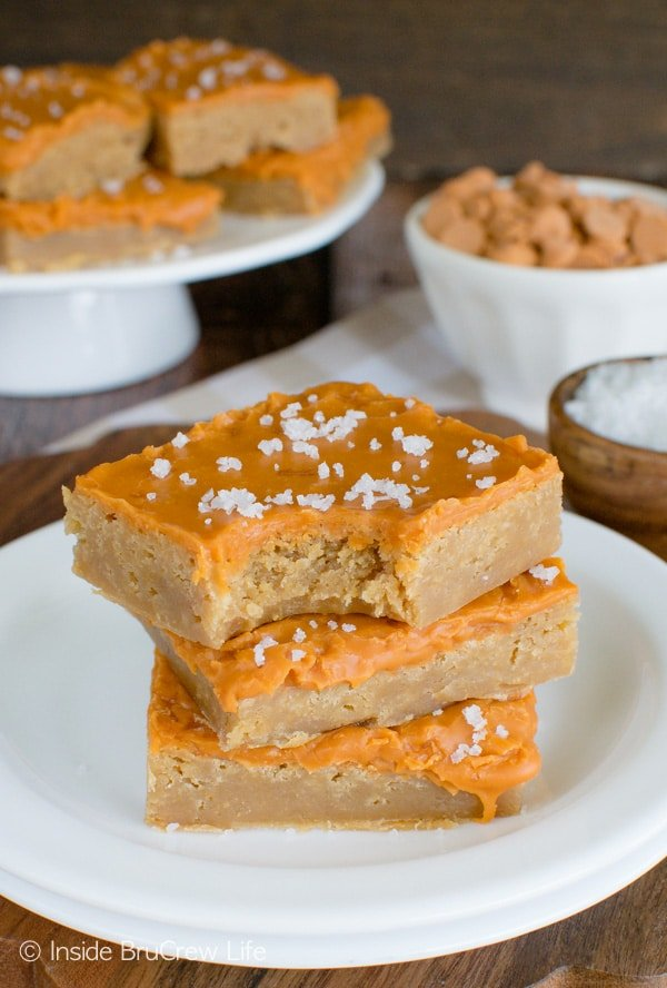 Three salted butterscotch bars on a white plate with a bite out of the top bar