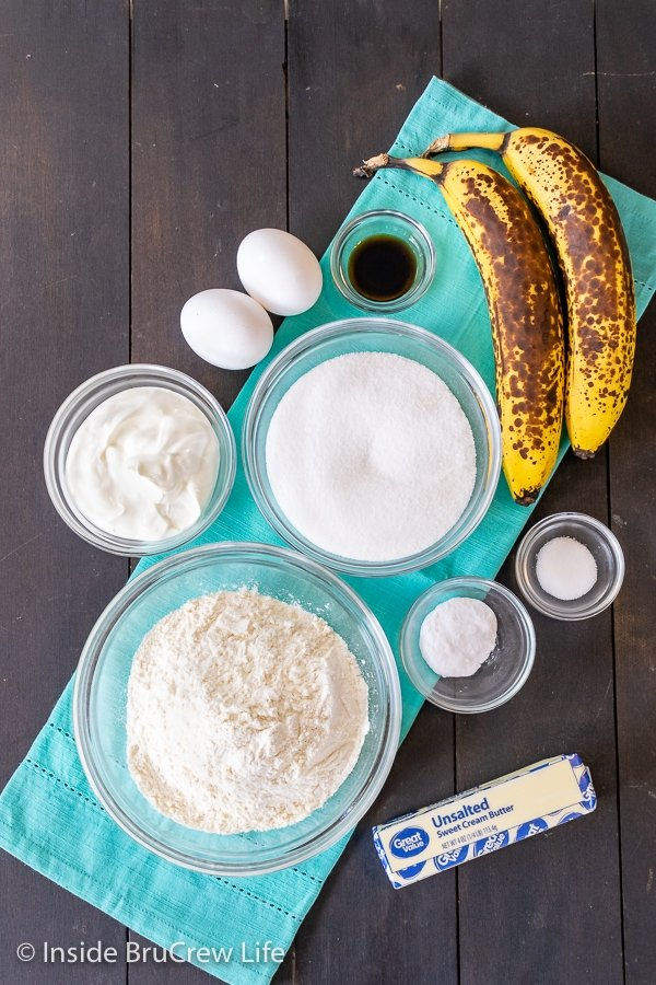 Ingredients needed to make sour cream banana bread on a dark board