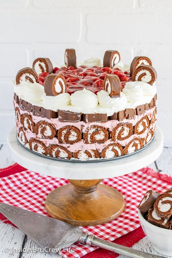 A white cake plate with a full No Bake Cherry Swiss Rolls Cake on it topped with cherry pie filling