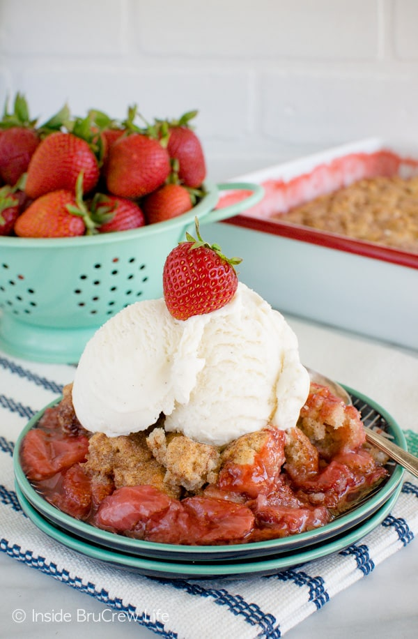 A plate filled with strawberry cobbler and topped with a scoop of vanilla ice cream and the pan of cobbler behind it