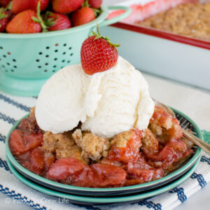 A plate filled with strawberry cobbler and topped with a scoop of vanilla ice cream