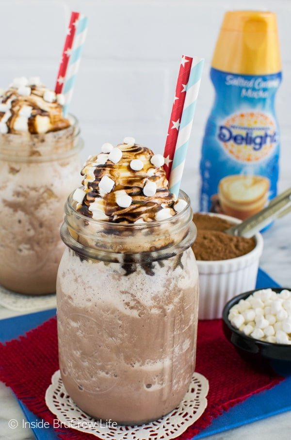 Two glasses filled with Frozen Salted Caramel Mocha Hot Chocolate with bowls of hot chocolate mix and marshmallows behind them