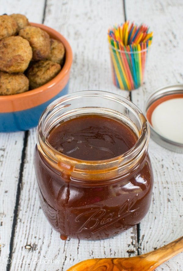 A jar of honey sriracha barbecue sauce with a bowl of baked meatballs behind it