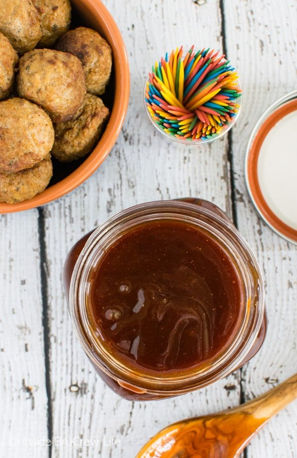 An overhead picture of a jar of honey sriracha barbecue sauce and a bowl of baked meatballs