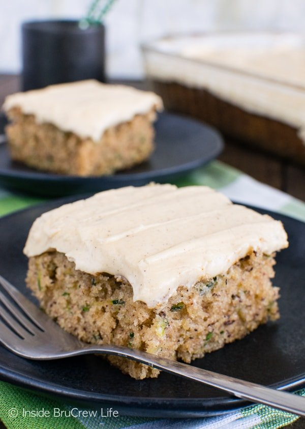 Two black plates with squares of zucchini banana cake topped with caramel frosting on them