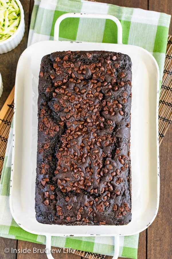 Overhead picture of a loaf of chocolate zucchini bread with chocolate chips on top on a white tray.