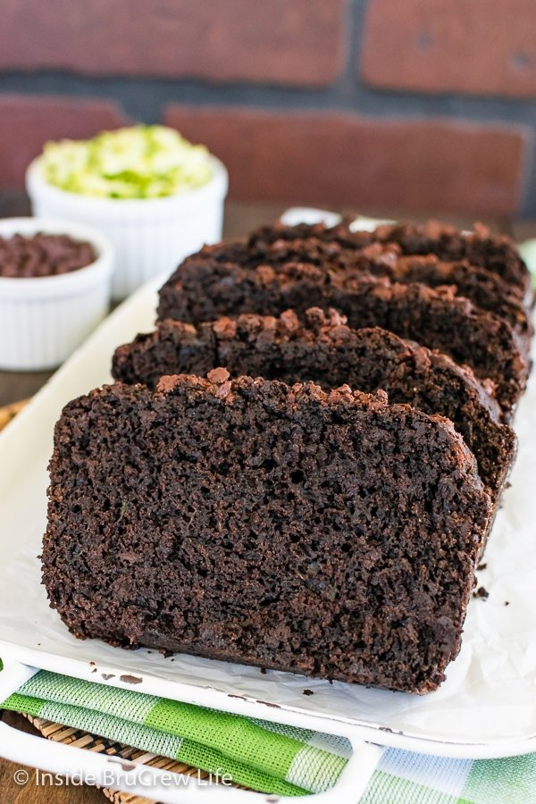 Slices of chocolate zucchini bread on a white tray.