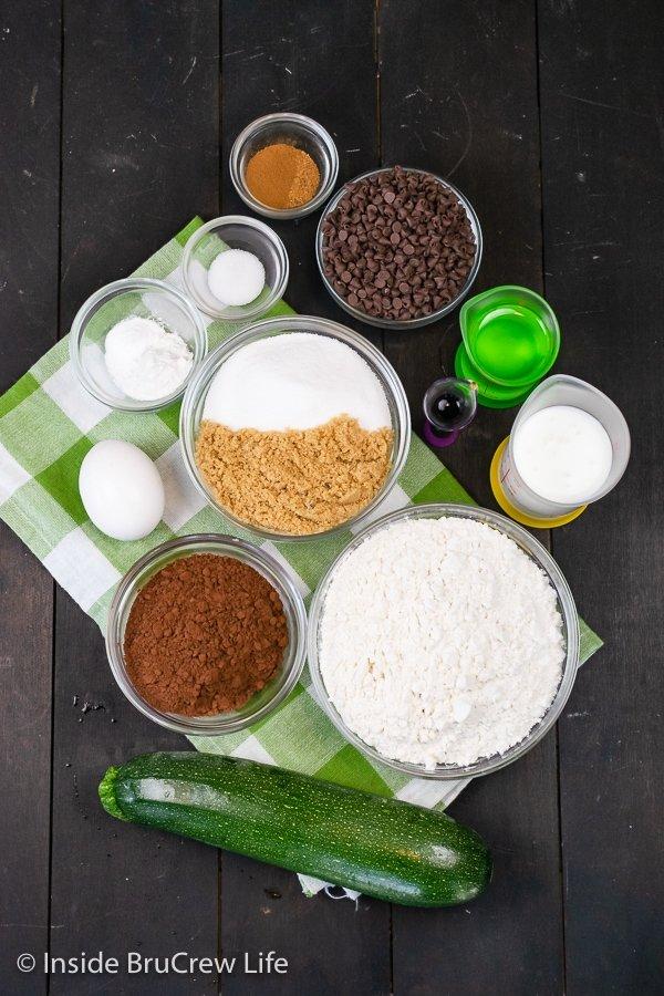 A dark board with bowls of ingredients to make a dark chocolate zucchini bread.