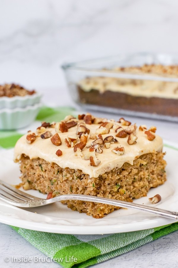 A white plate with a slice of zucchini banana cake topped with caramel frosting and chopped pecans.