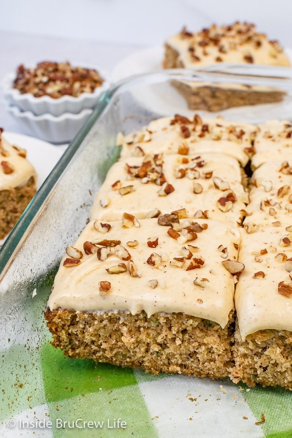 A glass cake plate filled with zucchini banana cake topped with caramel frosting.
