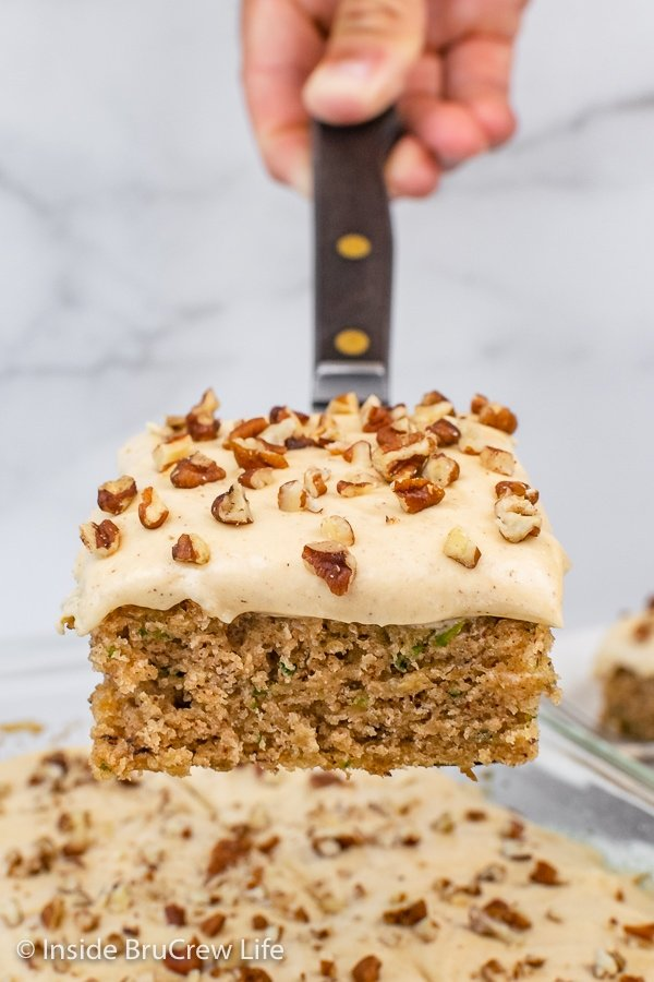 A spatula lifting a square of frosted zucchini cake out of a cake pan.