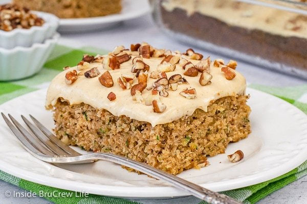 A white plate with a square of zucchini cake topped with caramel frosting and pecans.