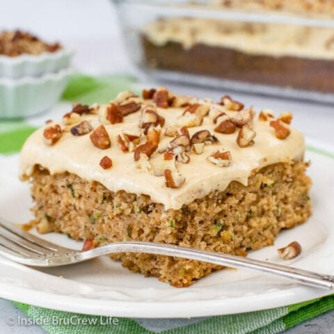 A white plate with a slice of zucchini banana cake topped with caramel frosting and pecans.