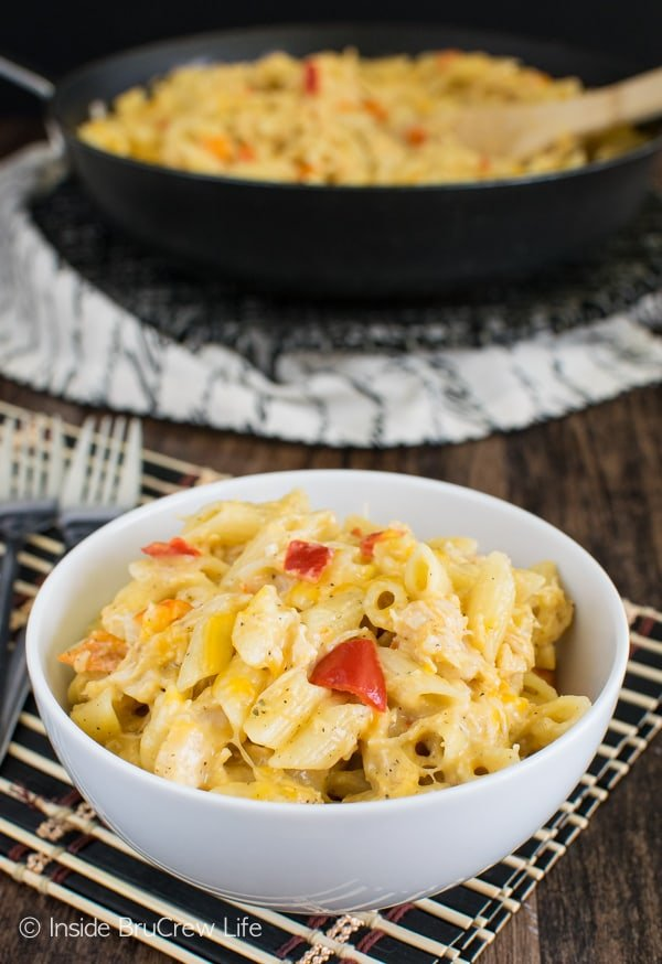 A white bowl filled with cheesy chicken pasta and the rest of the pasta behind it in a black skillet
