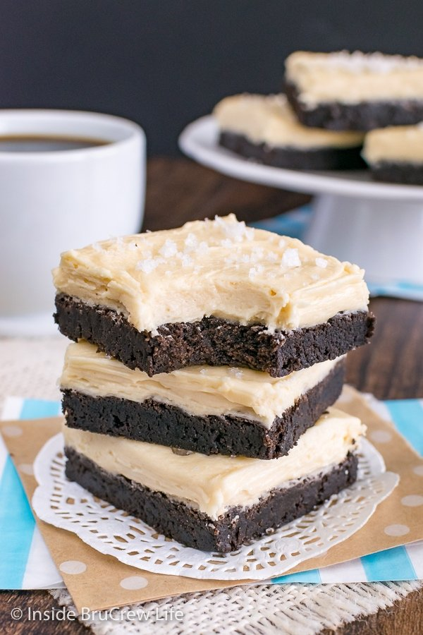 Three chocolate sugar cookie bars frosted with salted caramel frosting stacked on top of each other