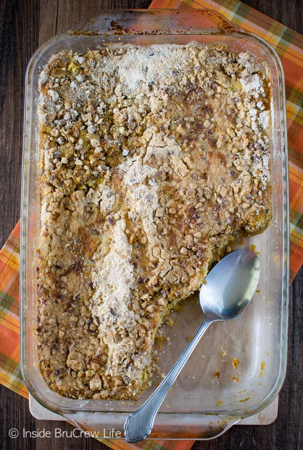 Overhead picture of a pan of pumpkin crunch cobbler with a few spoonfuls take out