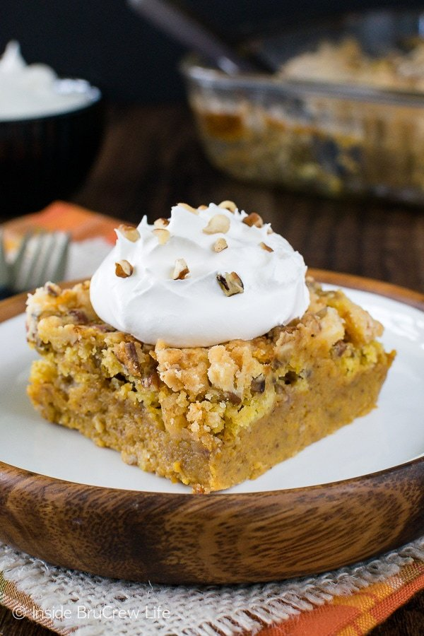 A brown and white plate with a square of pumpkin crunch cobbler topped with homemade whipped cream