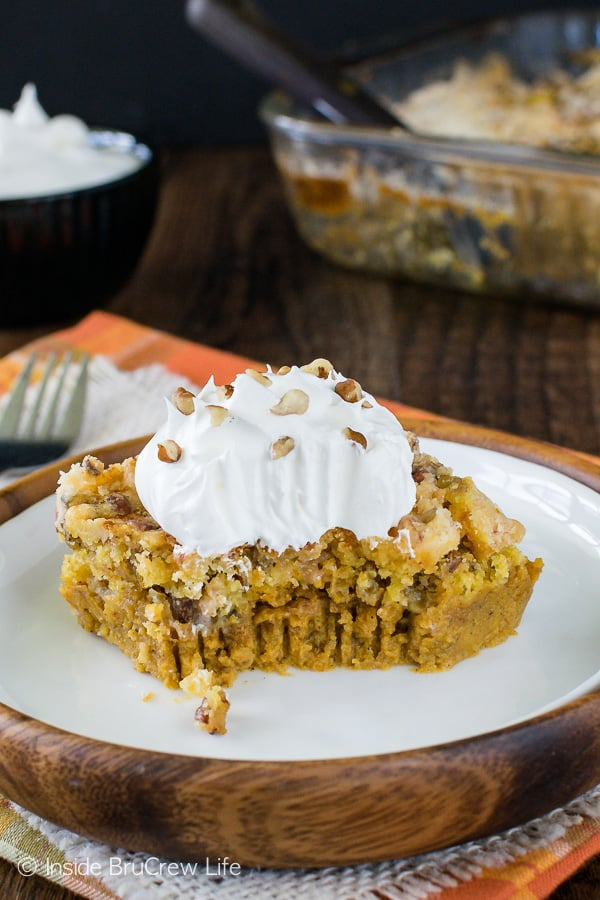 A square of pumpkin cobbler with whipped cream on a white plate with a bite take out of it