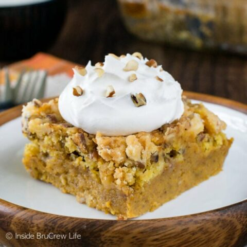 A white plate with a piece of pumpkin crunch cobbler with whipped cream on it.