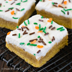 Frosted pumpkin spice sugar cookie bars on a black wire rack