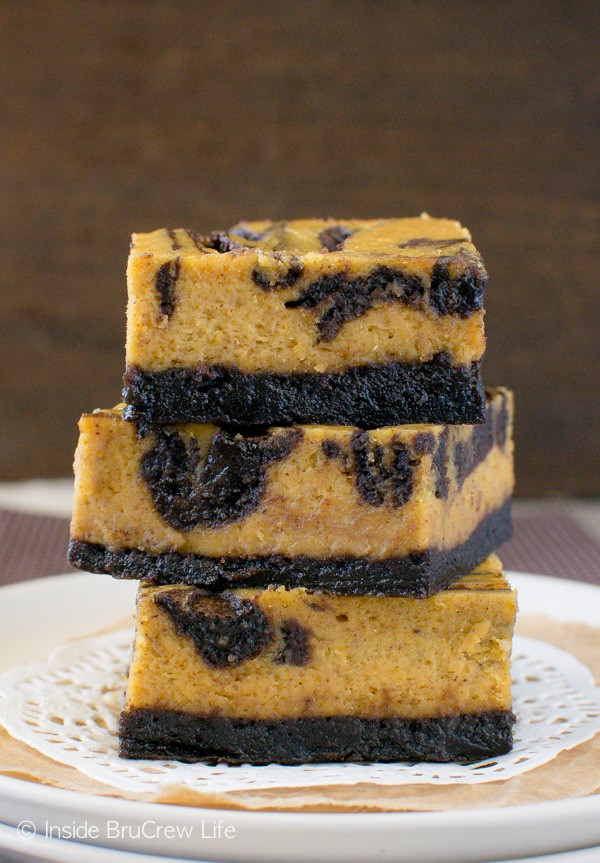 Brownie Swirled Pumpkin Cheesecake Bars - a chocolate crust pairs so well with the creamy pumpkin spice cheesecake. Great dessert recipe for fall parties.