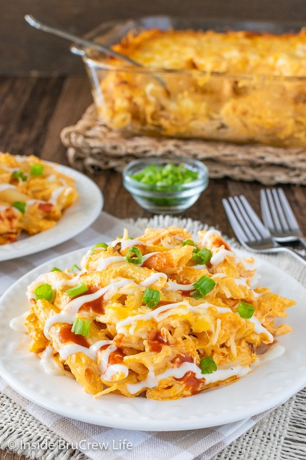 Close up picture of buffalo chicken pasta bake on a white plate and a casserole dish of pasta behind it.
