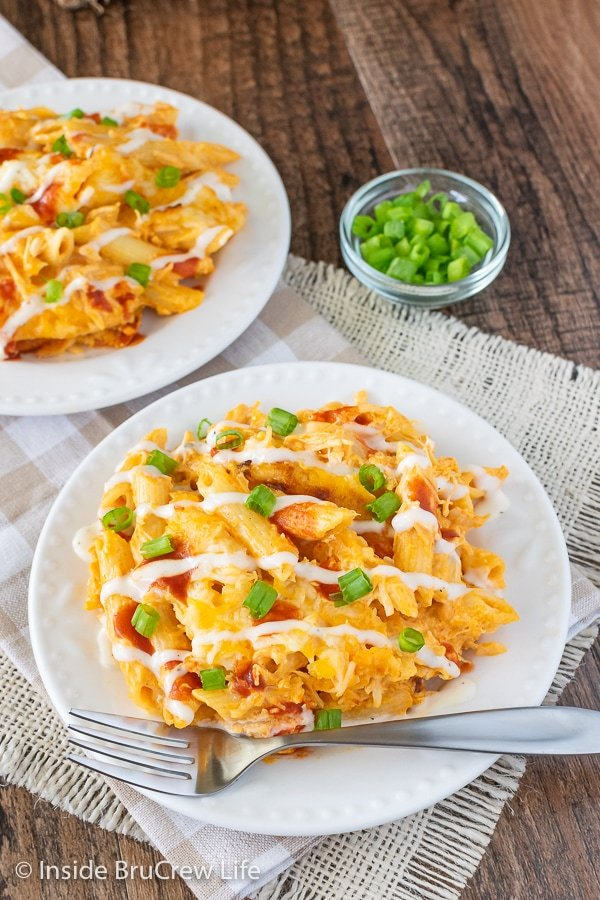 An overhead picture of a white plate with buffalo chicken pasta drizzled with ranch and hot sauce and green onions.