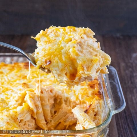 A casserole dish of buffalo chicken pasta with a spoon lifting pasta out.