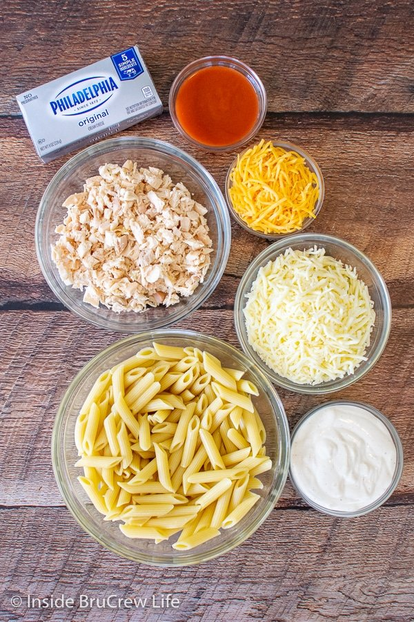 Bowls of ingredients to make buffalo chicken pasta bake on a wooden board.