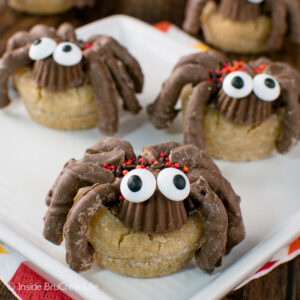 A white plate with three peanut butter cup spider cookies with candy eyes on it
