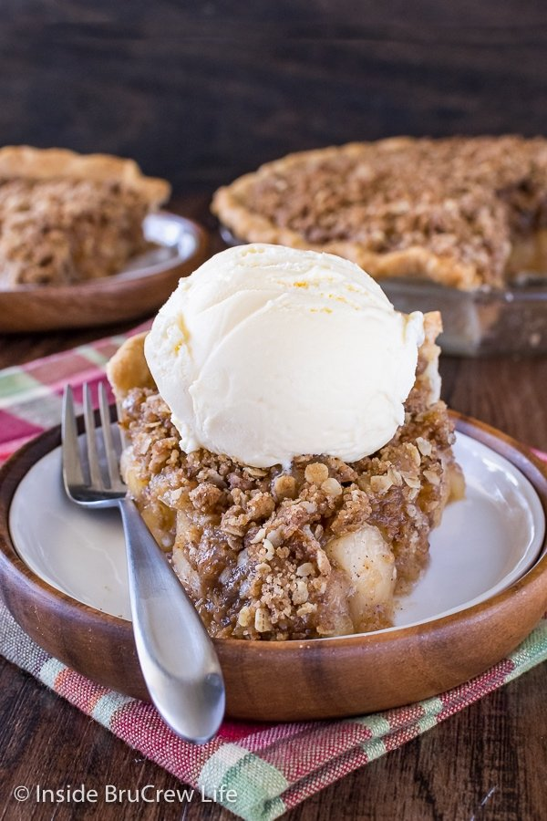 A slice of apple crisp pie topped with vanilla ice cream on a white plate
