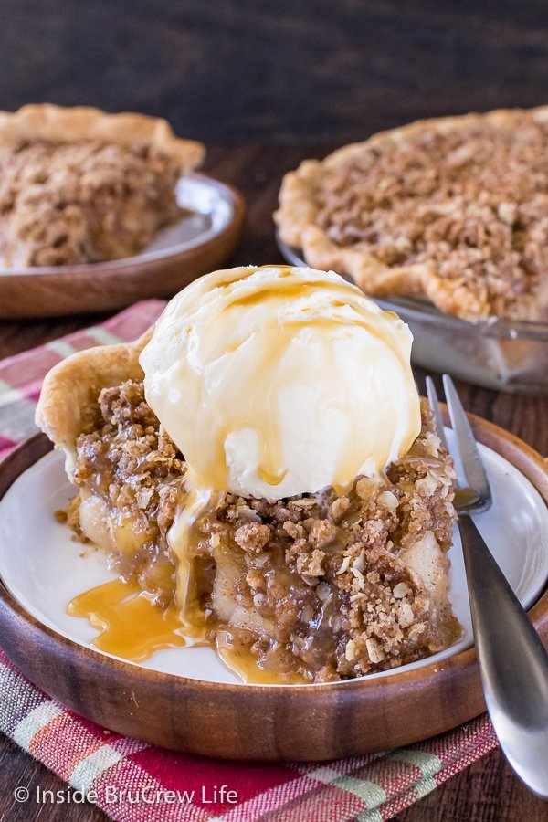 A white and brown plate with a slice of apple crisp pie topped with vanilla ice cream and caramel drizzles