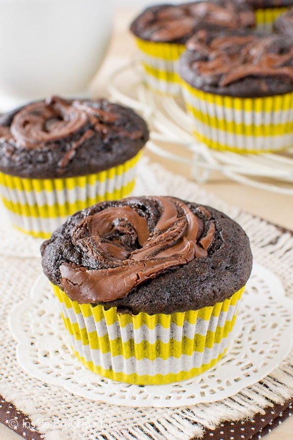 Two chocolate nutella banana muffins in white and yellow liners sitting on white doilies
