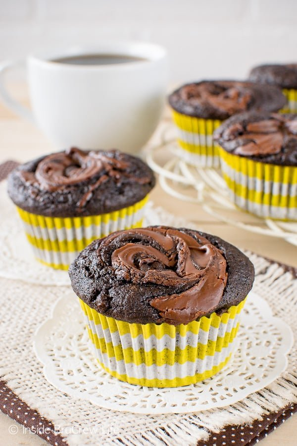 Two chocolate nutella banana muffins on white doilies with a tray of muffins behind them