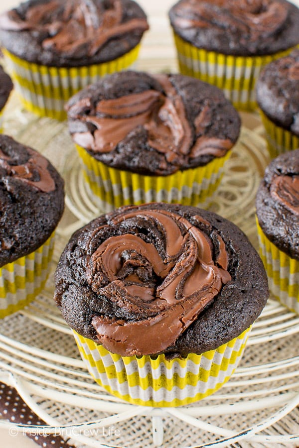 A close up picture of the top of a chocolate nutella banana muffin with more muffins behind it