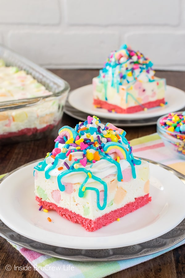 No Bake Rainbow Unicorn Cheesecake Bars - a bright pink cookie crust and lots of colorful marshmallows and sprinkles makes this easy dessert a fun recipe for spring!