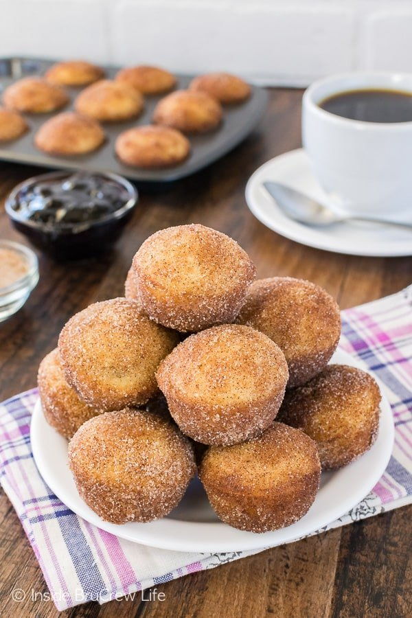 A pile of Blueberry Jelly Donut Holes on a white plate with coffee in the background