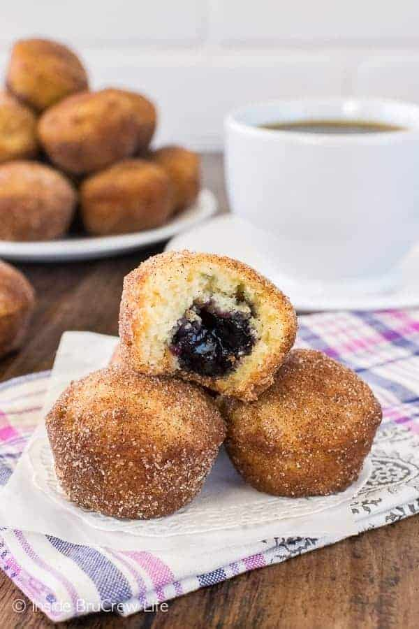A stack of blueberry jelly donut holes with a bite out of one on a white doily