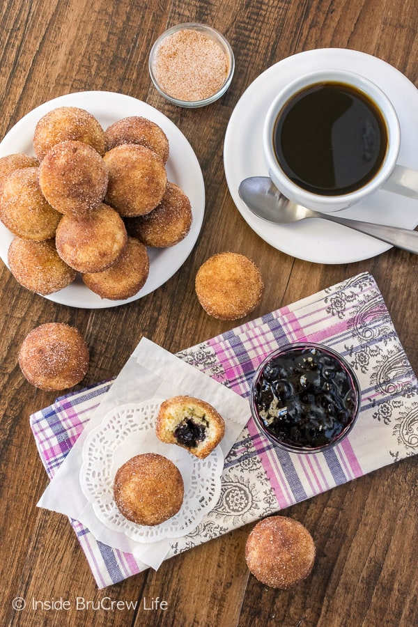 Overhead picture of blueberry jelly donut holes on white plates and white doiles