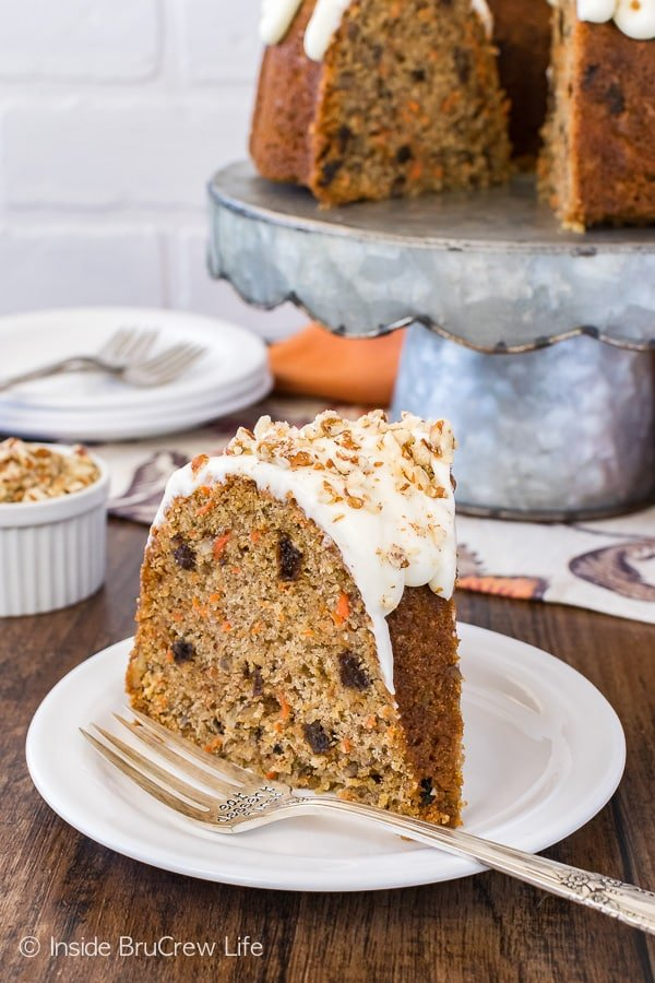 Carrot Bundt Cake - this soft homemade cake is loaded with lots of carrots, nuts, and raisins. Frosting adds the perfect touch to this easy cake recipe!