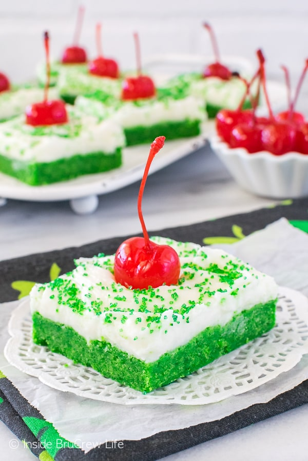 Shamrock Shake Sugar Cookie Bars - sweet mint cookie bars topped with white frosting & cherry to look like a shake. Easy dessert recipe to make for St. Patrick's day parties!