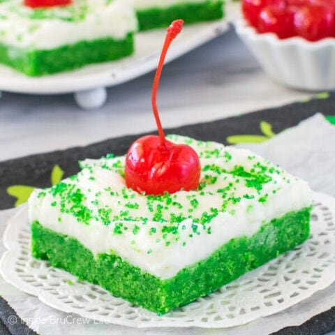 A white plate with a green shamrock shake sugar cookie bar topped with frosting, green sugar, and a cherry on it