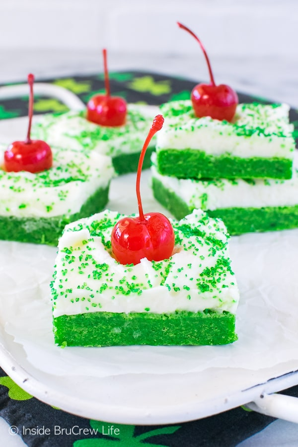 Shamrock Shake Sugar Cookie Bars - easy mint cookie bars topped with a creamy frosting. Add green sugar and a cherry to make them look like the popular shake! Great dessert recipe for St. Patrick's day parties!