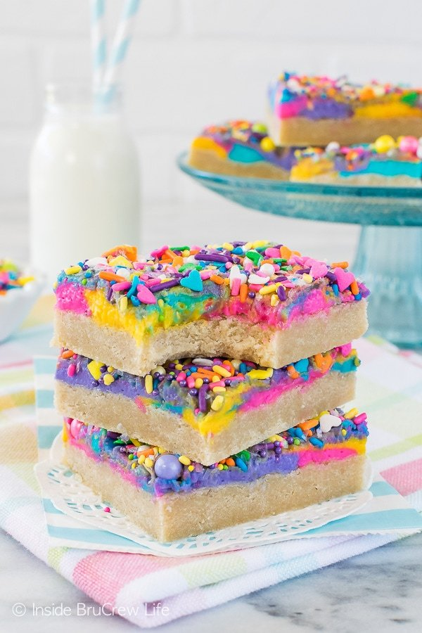 Three sugar cookie bars frosted with colorful vanilla frosting and sprinkles stacked on top of each other with a bite out of the top one