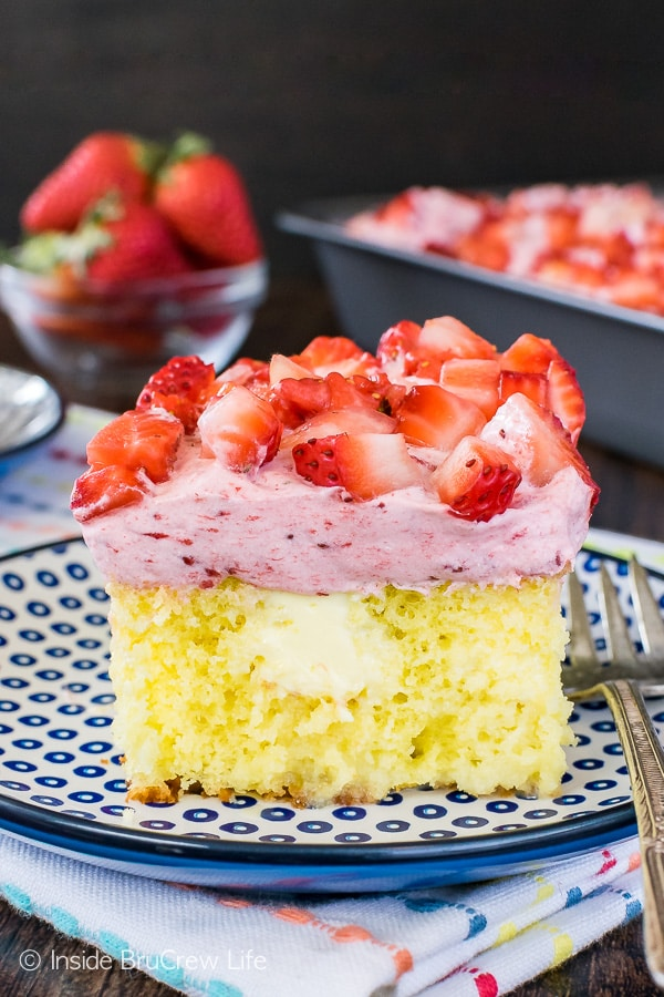 A close up pictures of a square of lemon strawberry poke cake on a blue and white plate