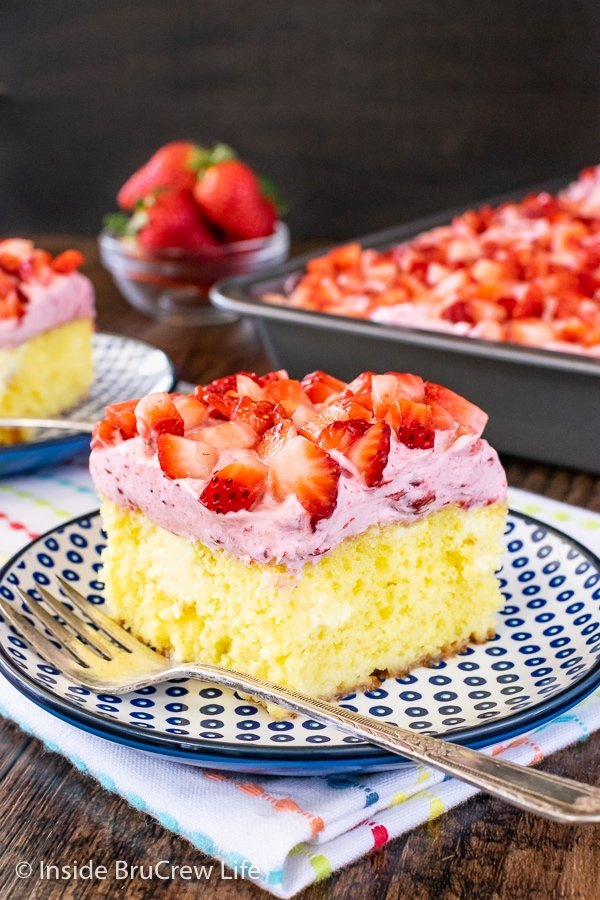 A slice of Lemon Strawberry Poke Cake on a blue and white plate with the cake behind it.